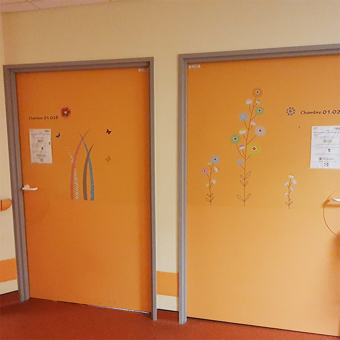 Porte de chambre de l'hôpital de Flers décorée avec des des stickers fleurs et herbe